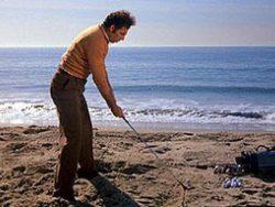 Kramer hitting a golf ball into the ocean.